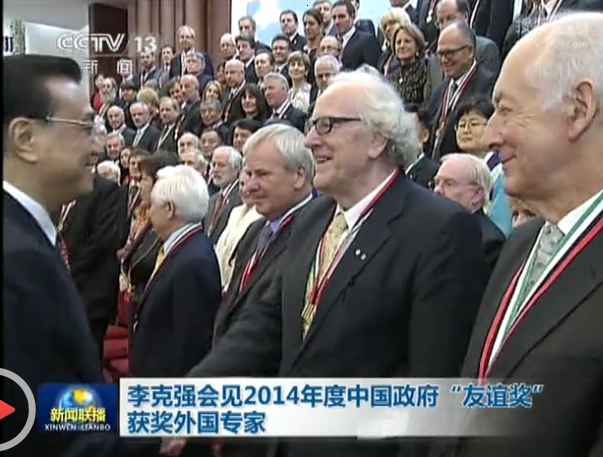Premier Li Keqiang shales Colin Mackerras's hand at the Friendship Award Ceremony. October 1 2014.