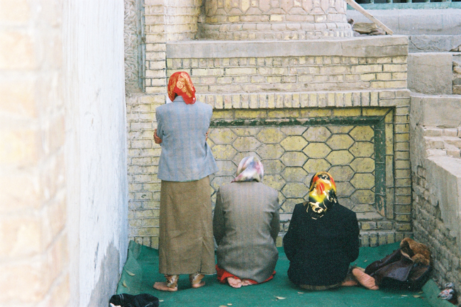 Xinjiang Muslim tradition does not allow women to pray in the main prayer-hall of a mosque. These three women are praying outside the Golden Mosque, Yarkant