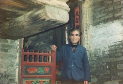 A Yao man in front of his house in Jinxiu, Guangxi, taken early in 1992. The man's clothes are modern, his house in traditional style.