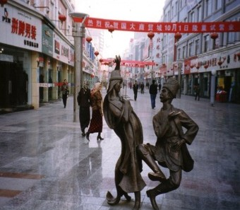In Aksu, central Xinjiang, is a modernized mall. In the foreground is an image of a Uygur pair dancing