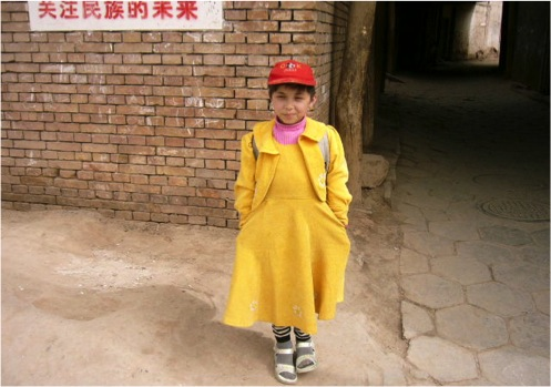 "Uygur girl in the old streets of Kashgar, 2007. The sign reads ""show solicitude for the nationality's future"""