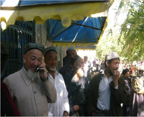 Outside the Hotan mosque Colin spoke to the imam (left), but, a modern man, he took a call on his mobile during the interview. Nearby are others, including an old Uygur with a very long beard.